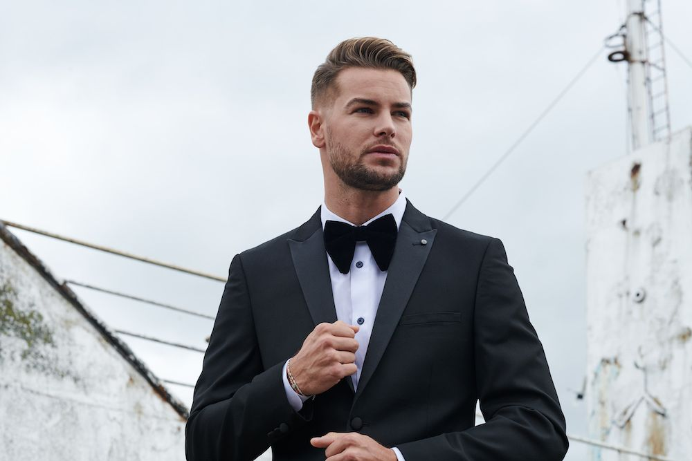 chris hughes wearing a suit and bow tie, looking into the distance