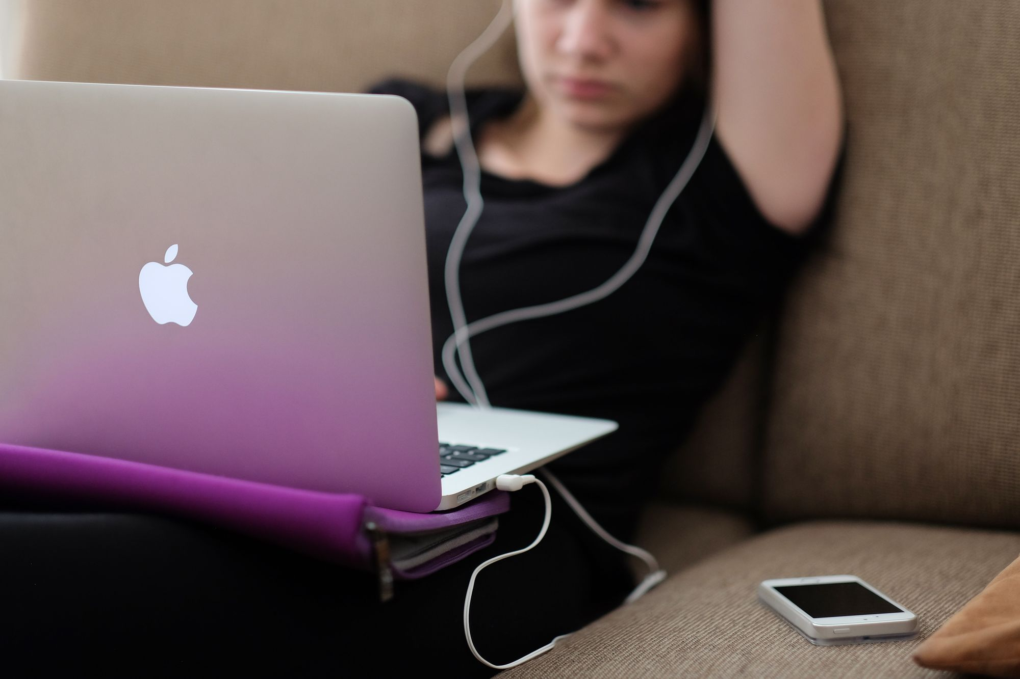 A teen sits alone on the sofa, watching porn on her laptop with her headphones in.