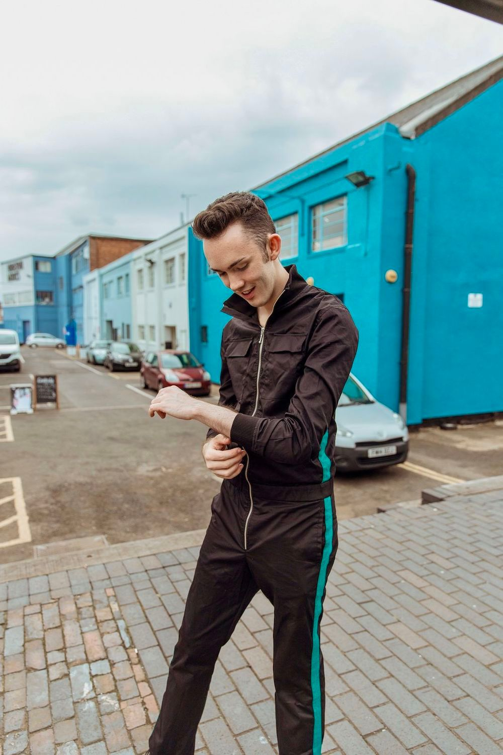 Jack standing and smiling infront of bright buildings