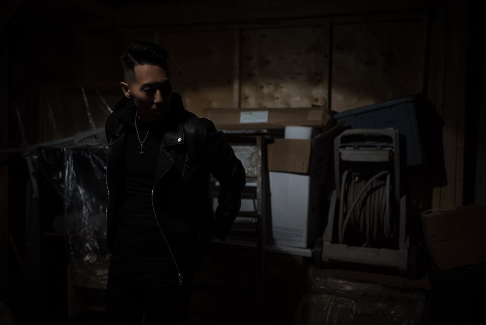 Andrew Yang standing in a dark room wearing a leather jacket