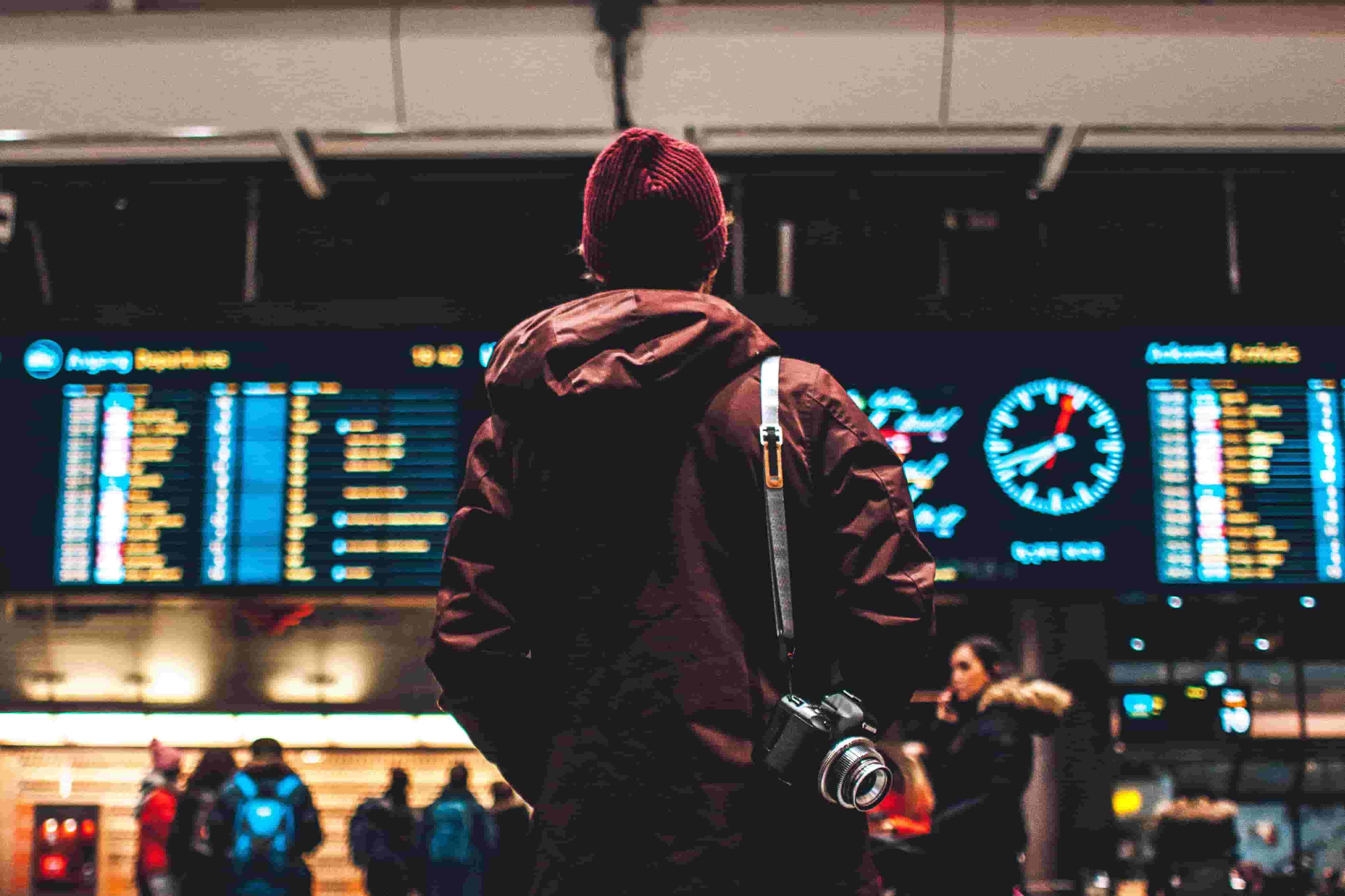 A man waits, looking up at the departure boards at the airport
