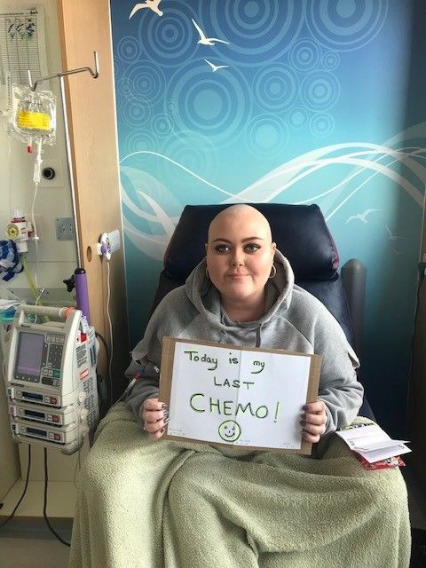 A photo of Alice smiling in hospital on her last day of chemotherapy