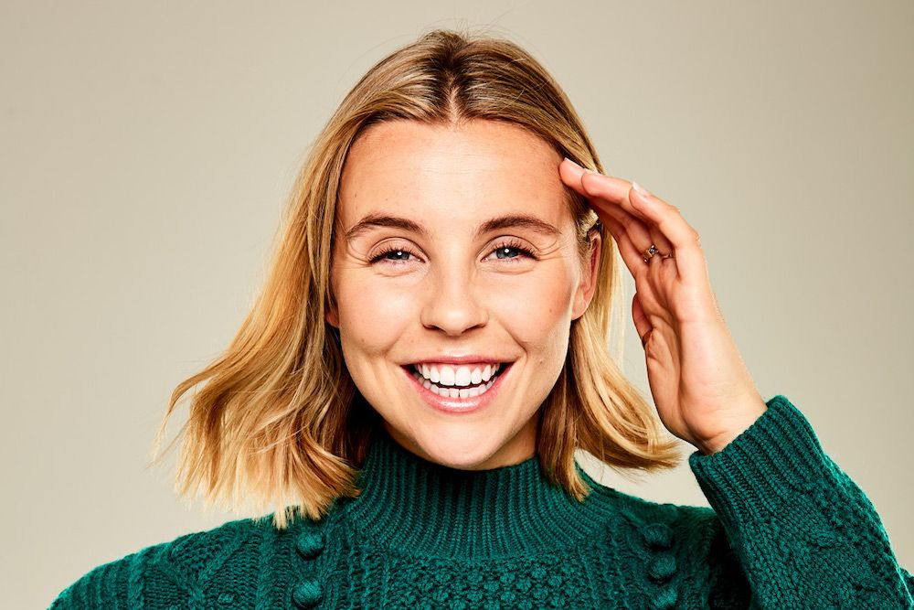 Chessie King smiling, wearing a teal knitted sweatshirt