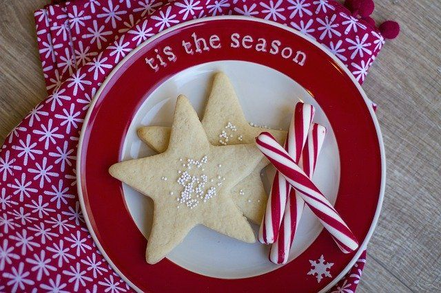 A close-up of peppermint sticks and star-shaped cookies on a plate that says 'tis the season'
