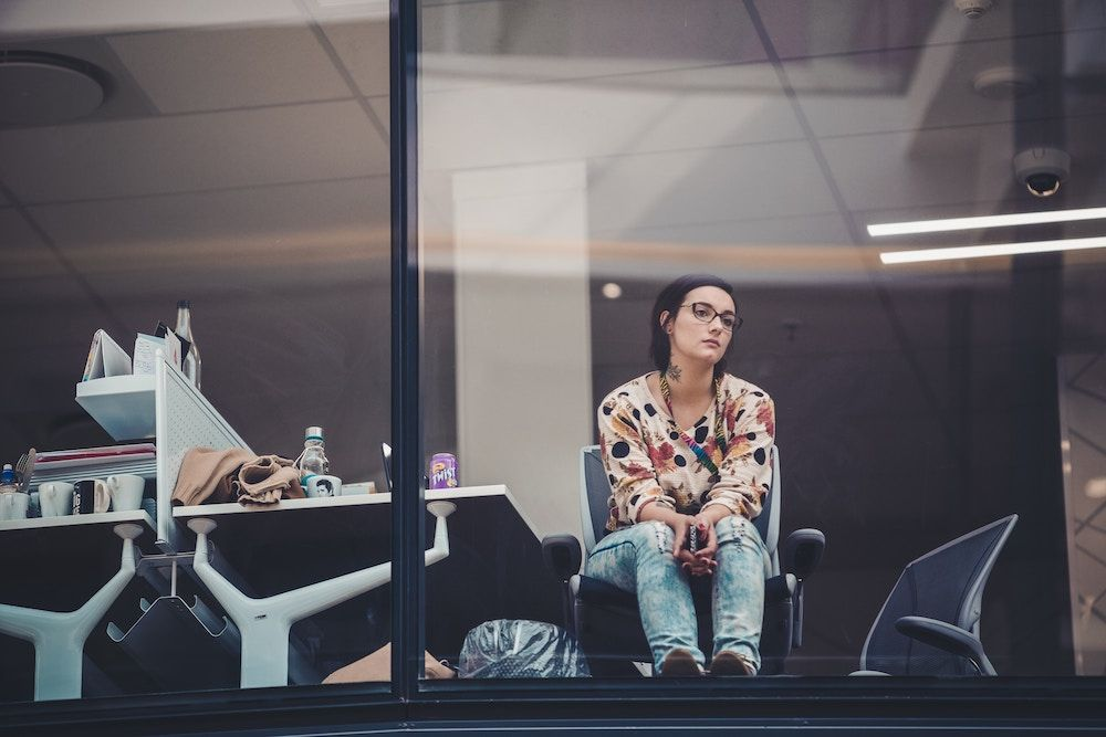 woman staring out the window at work wth a bored expression