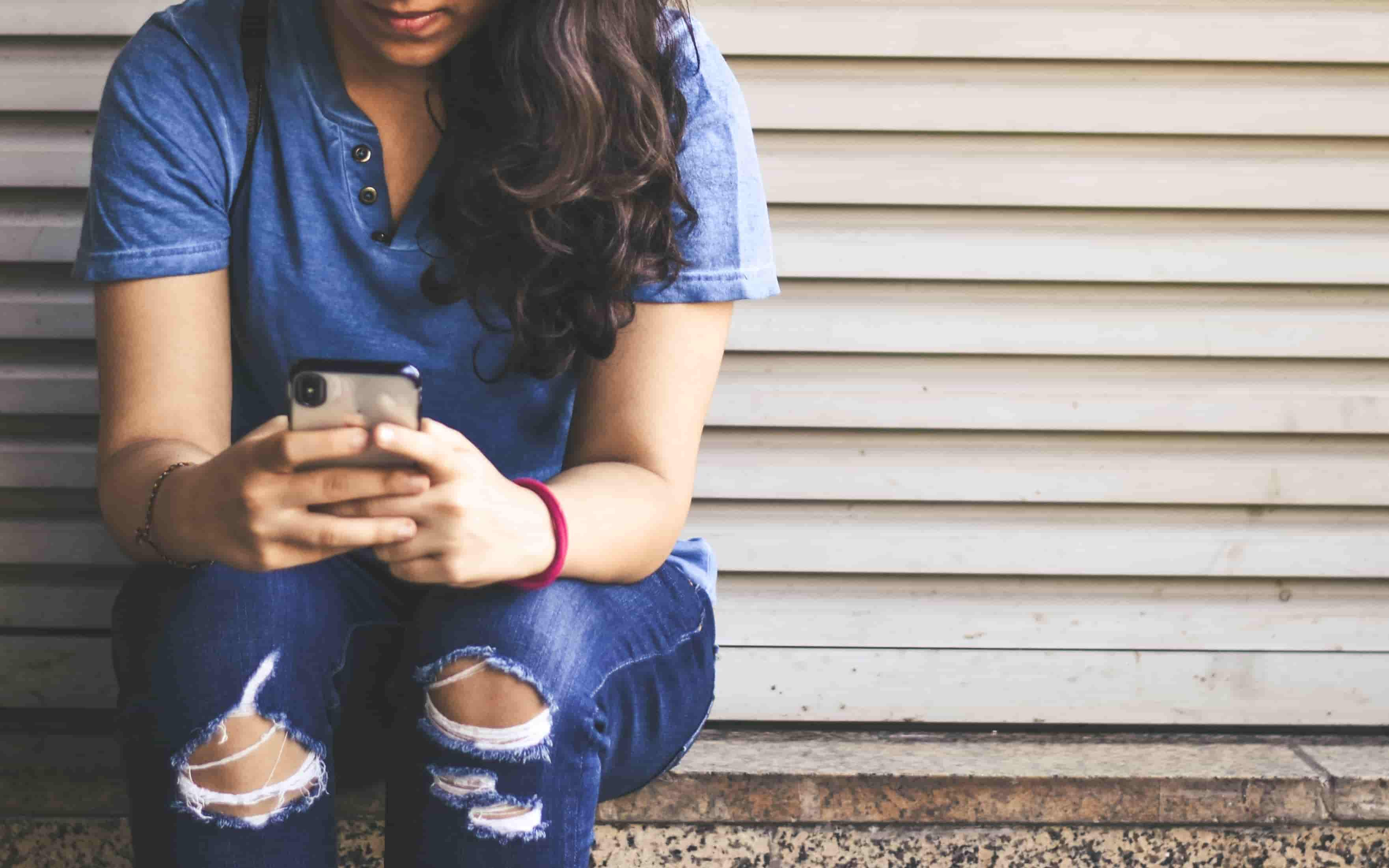 A woman sits outside on a step, holding her phone in both hands as she texts with a nervous look.