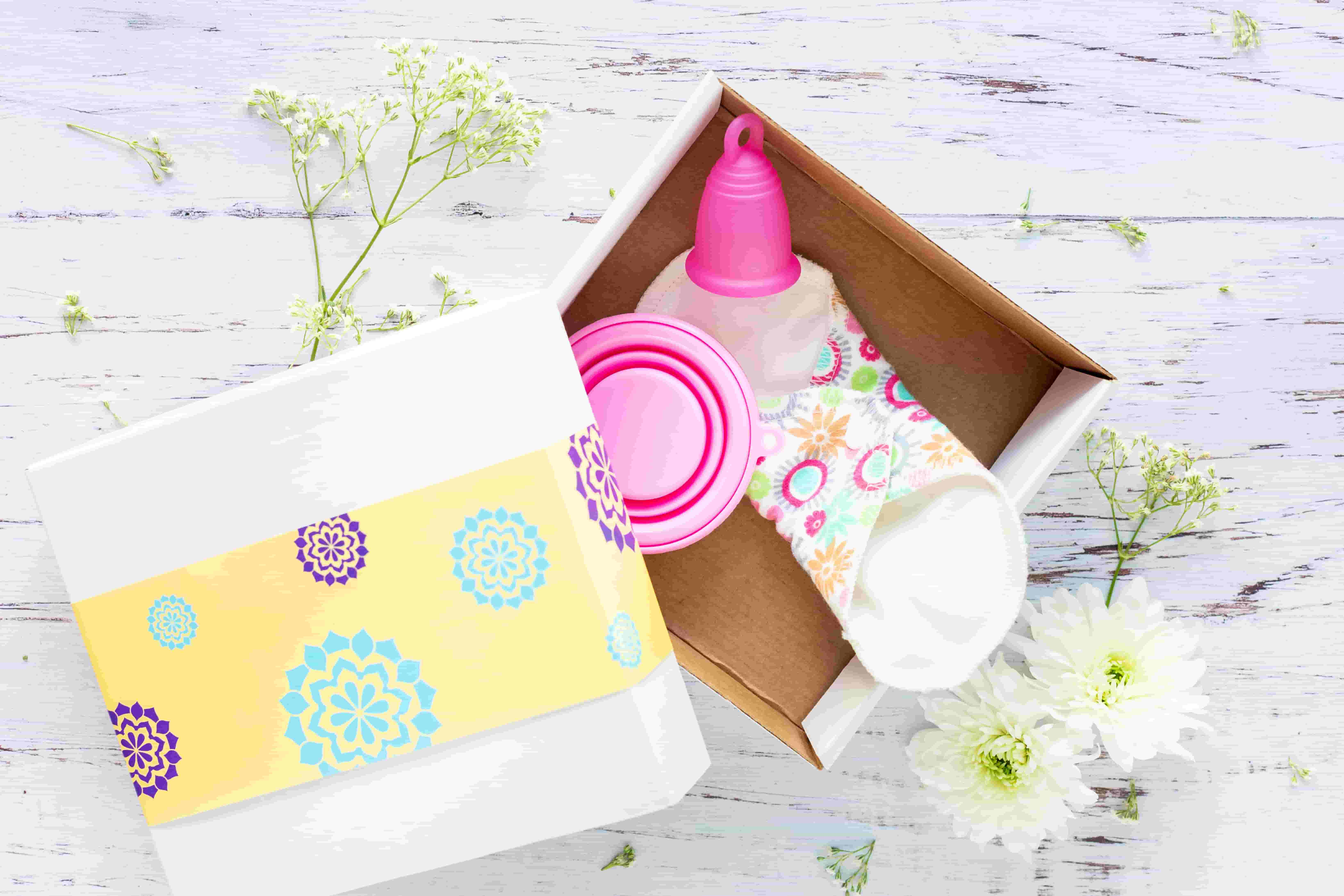 A box sits open with a reusable menstrual cup and pad within it