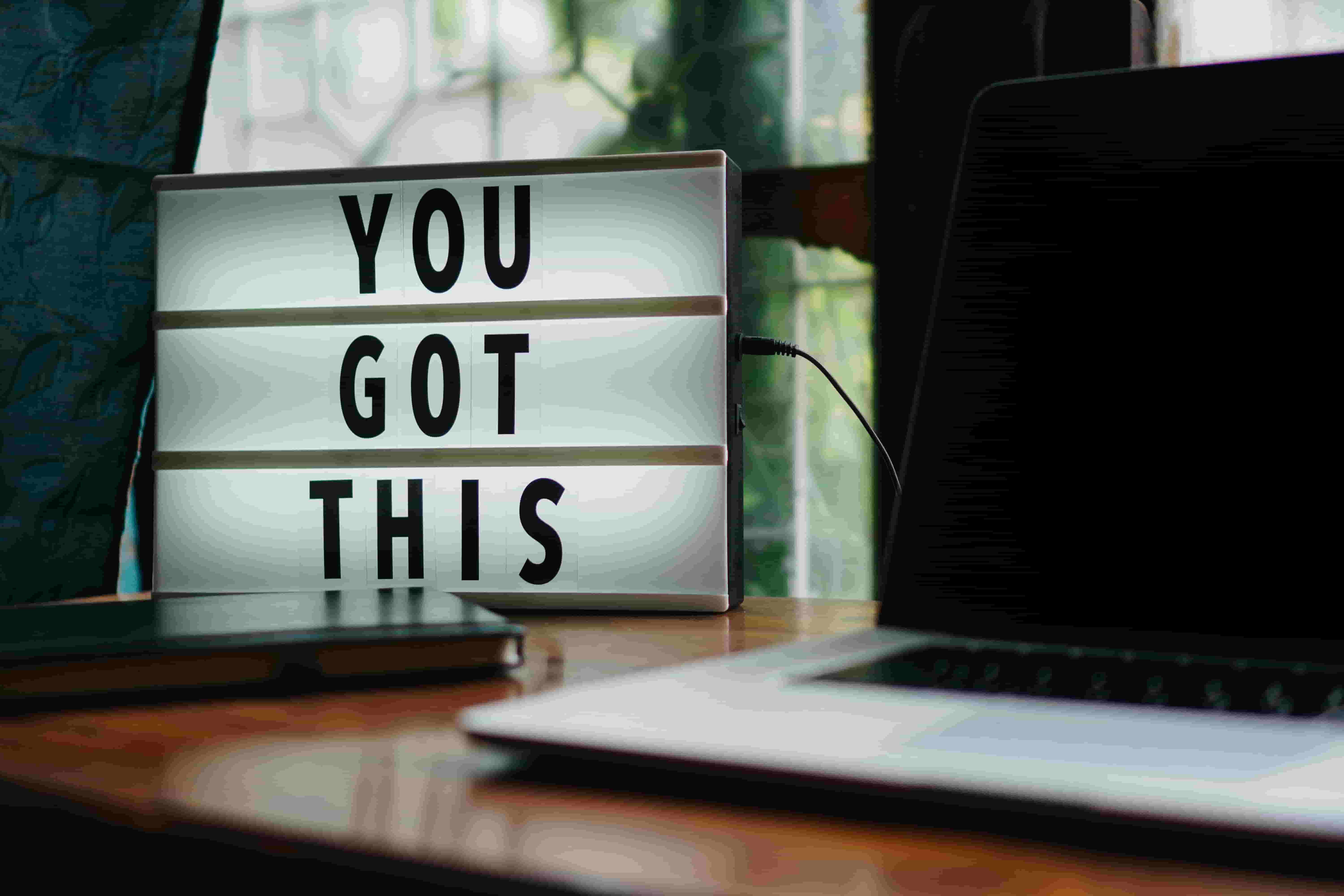 The words 'You Got This' are displayed on a light box next to a laptop