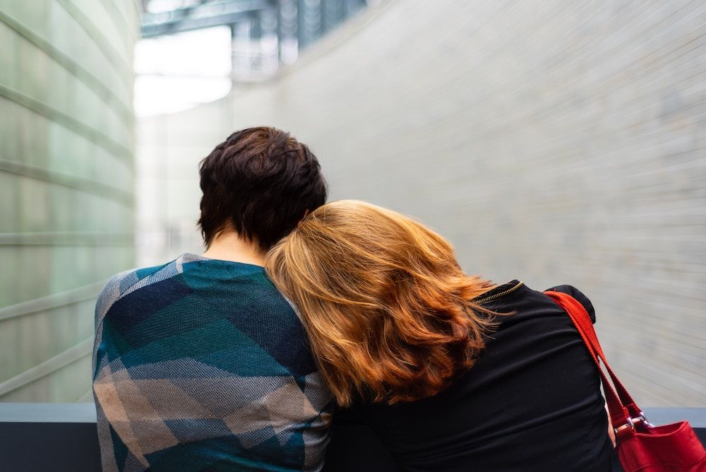 person resting head on their friends shoulder