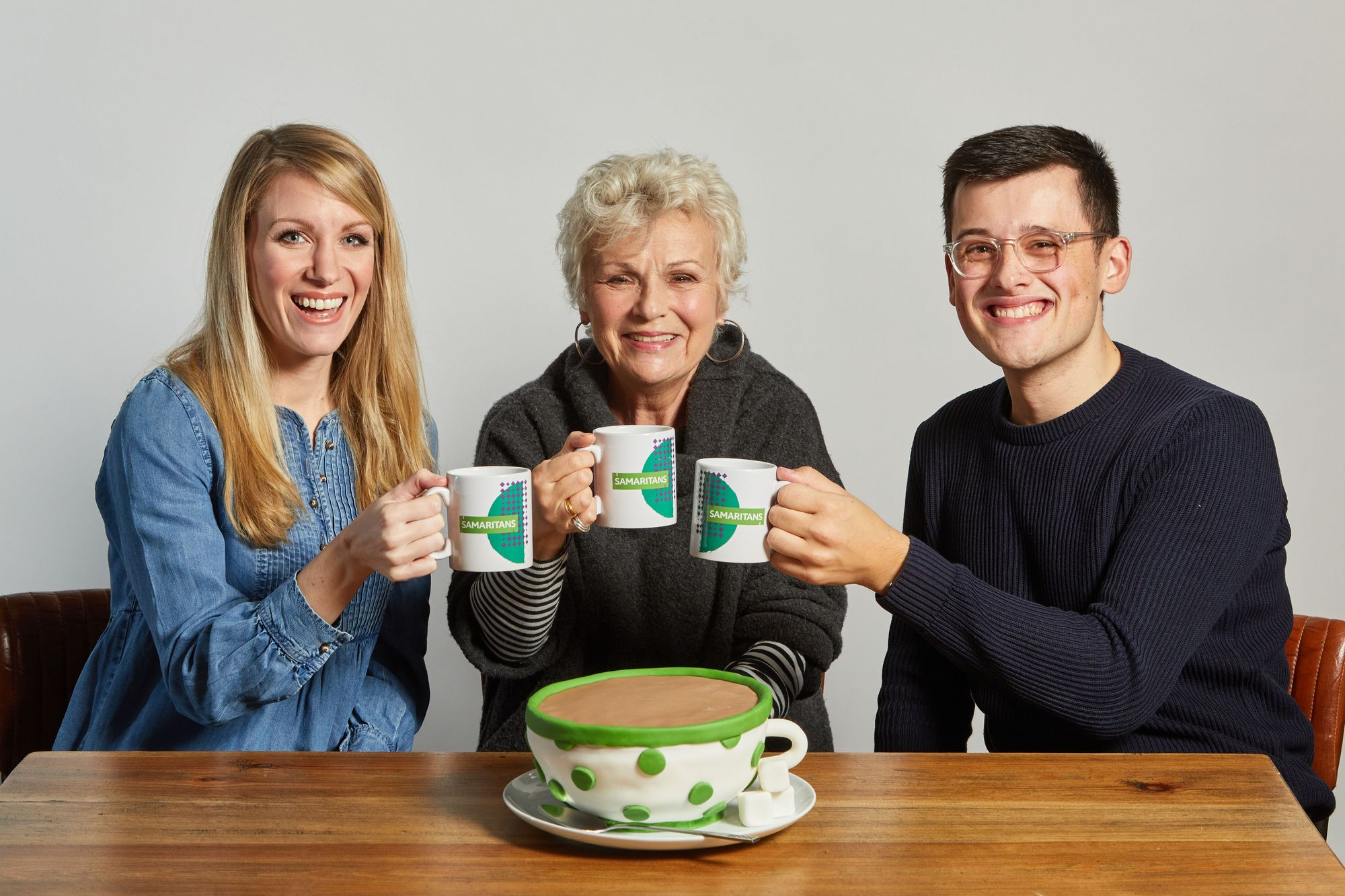 Dame Julie, Rachel and Michael share a cup of tea and pose with a teacup-shaped cake