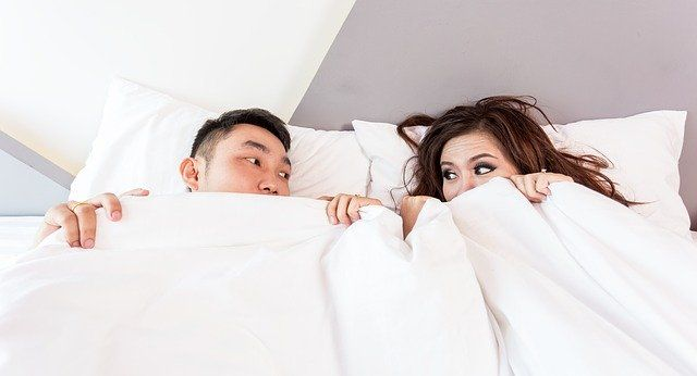 A couple look at each other nervously, peeking out from under a duvet