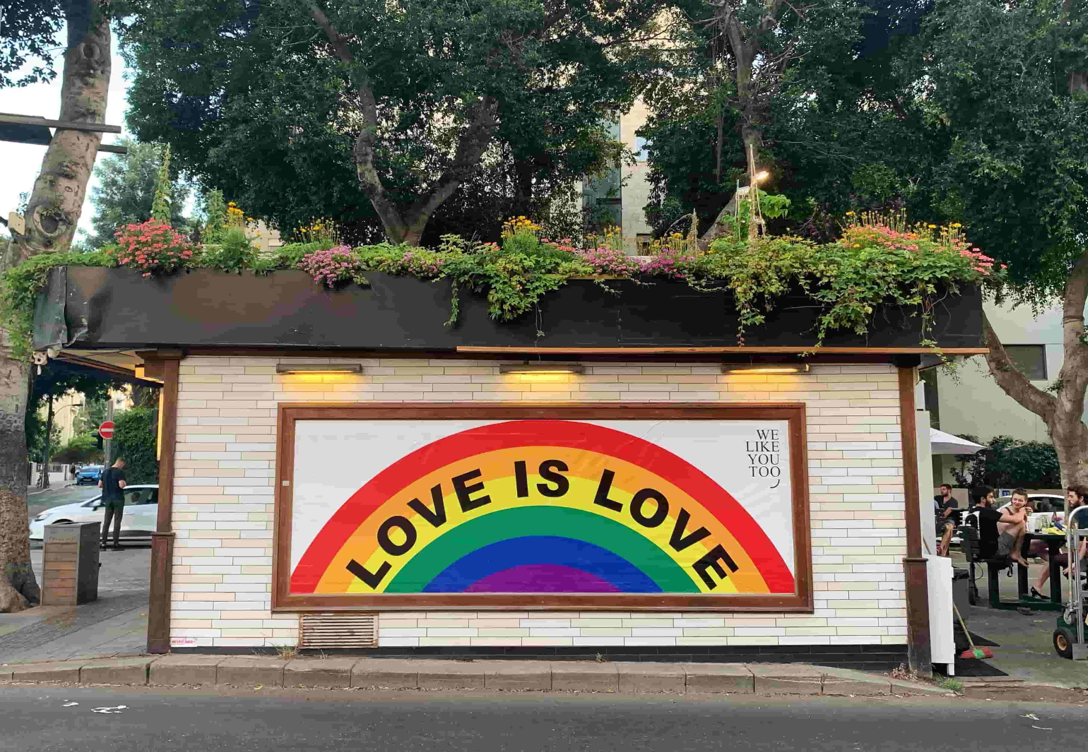 Close-up of a billboard, with 'Love is Love' written across a rainbow