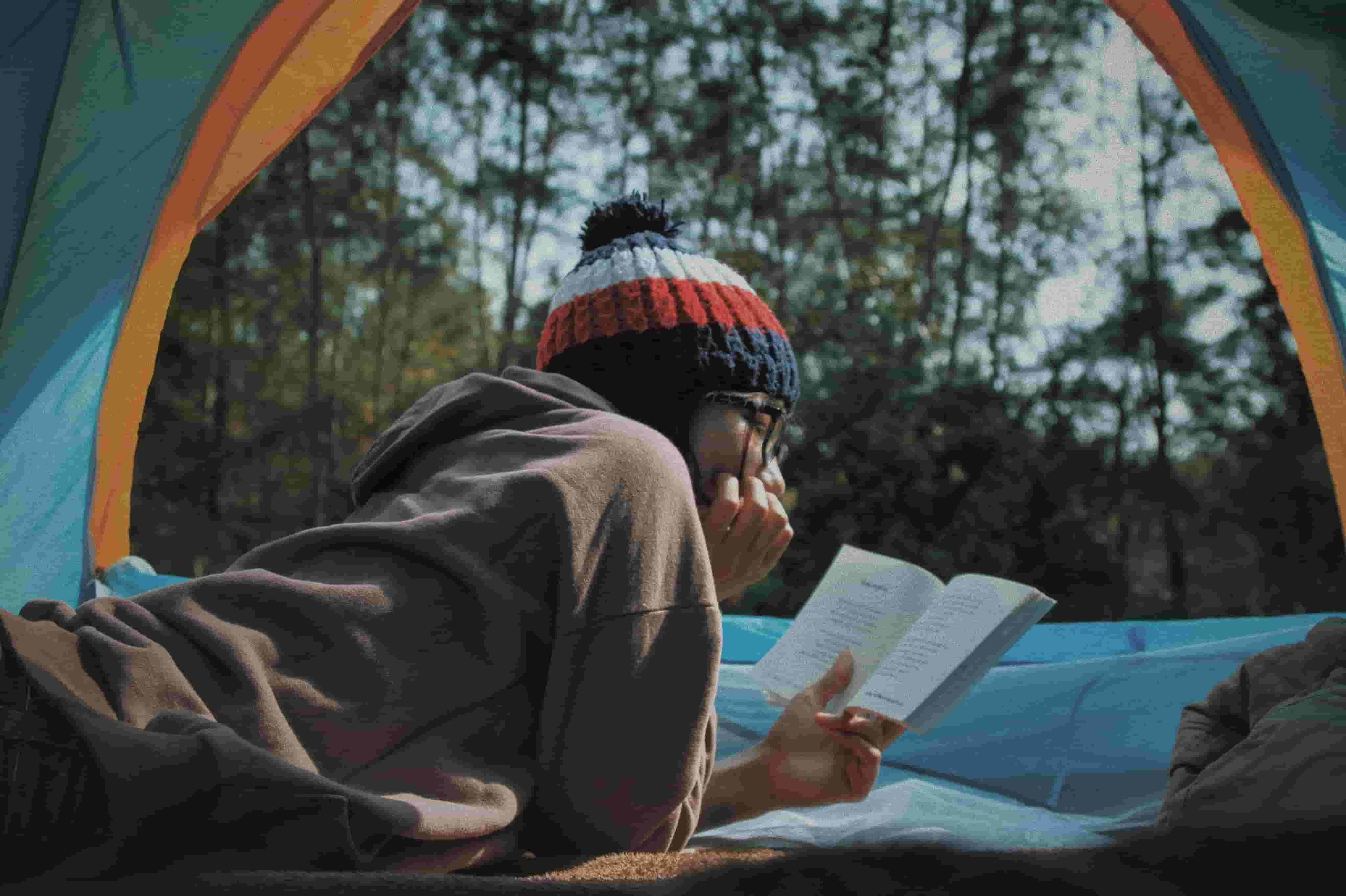 A woman reads whilst camping