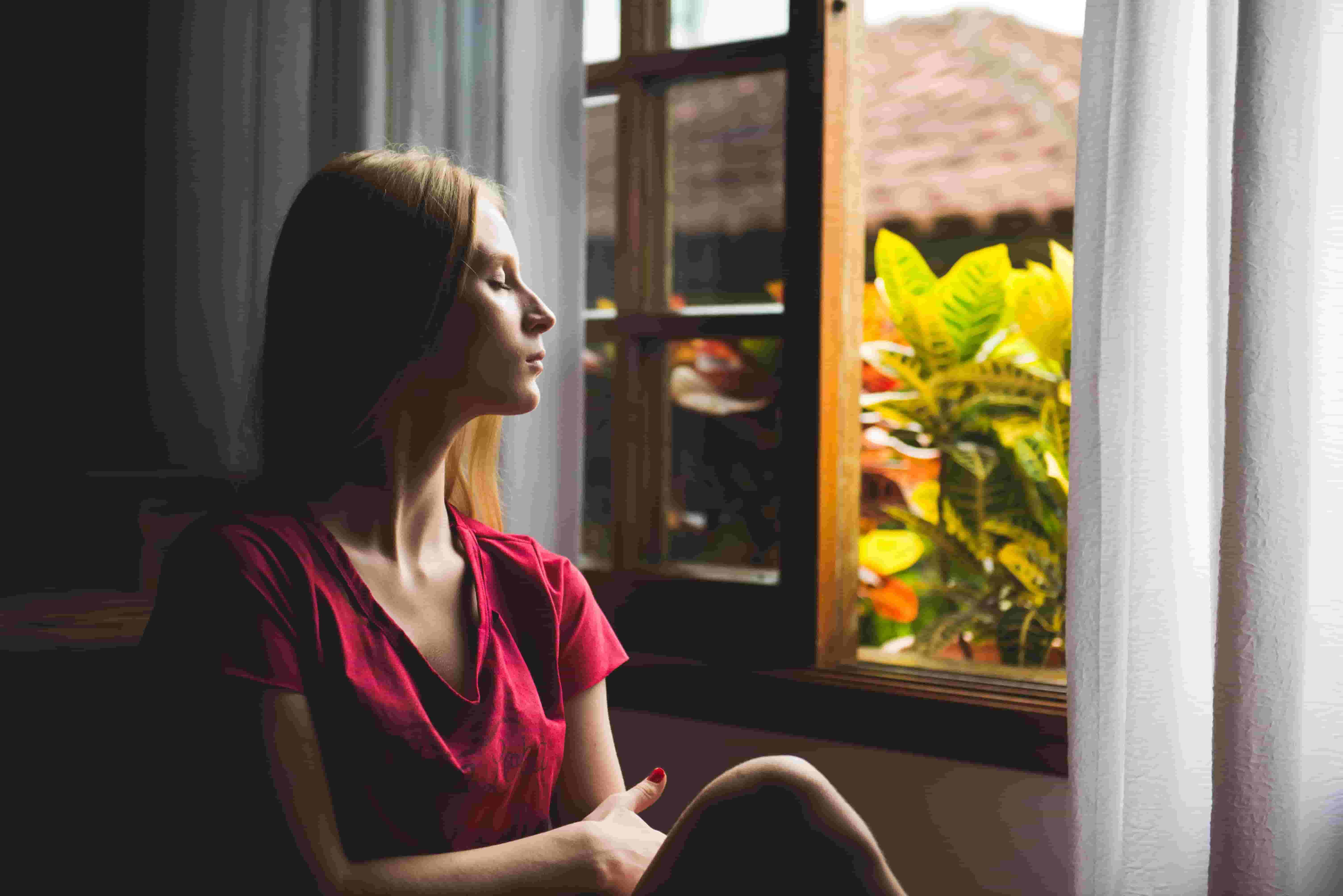 A woman sits by an open window, practicing mindfulness