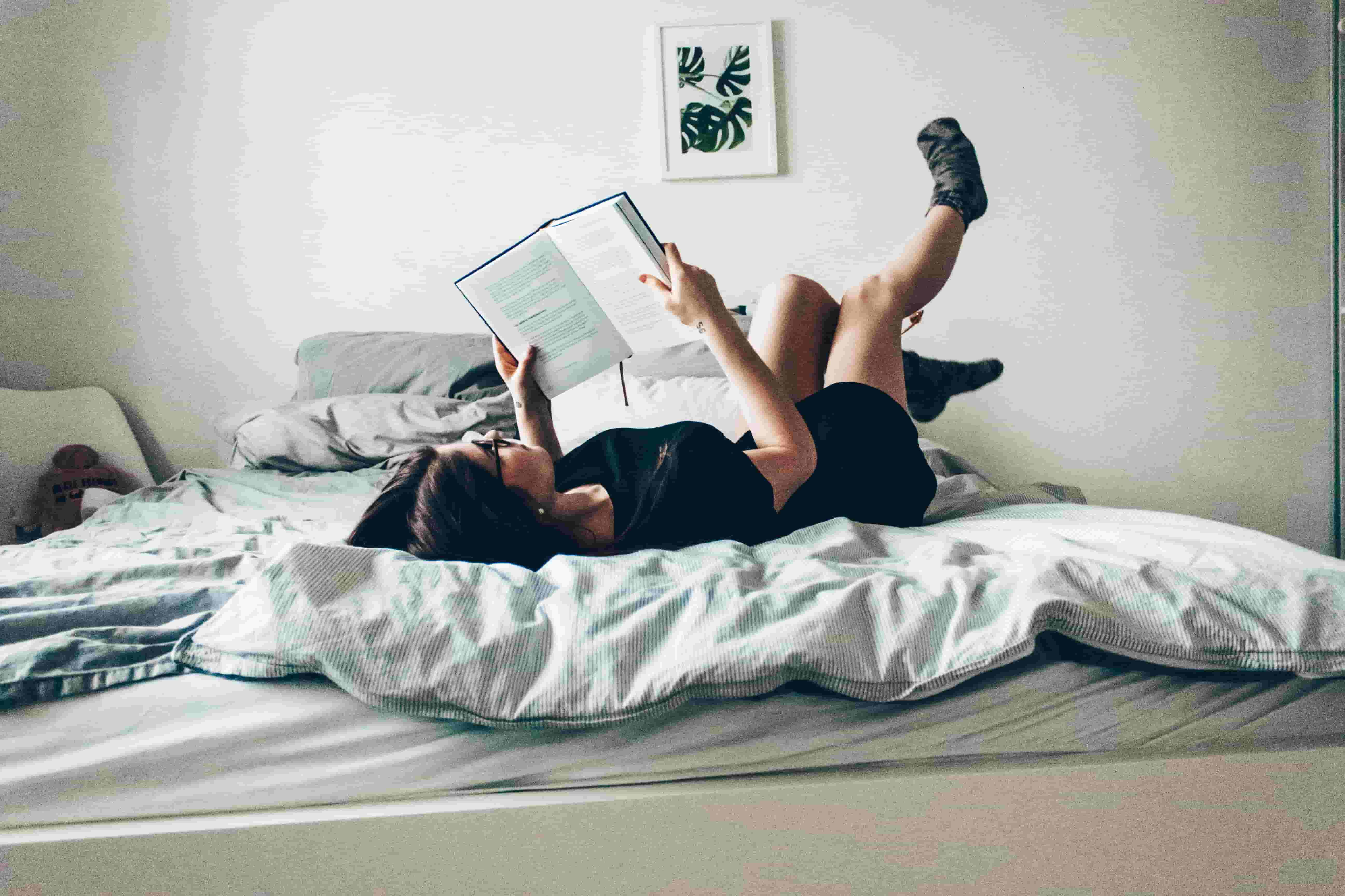 A woman lays in bed reading