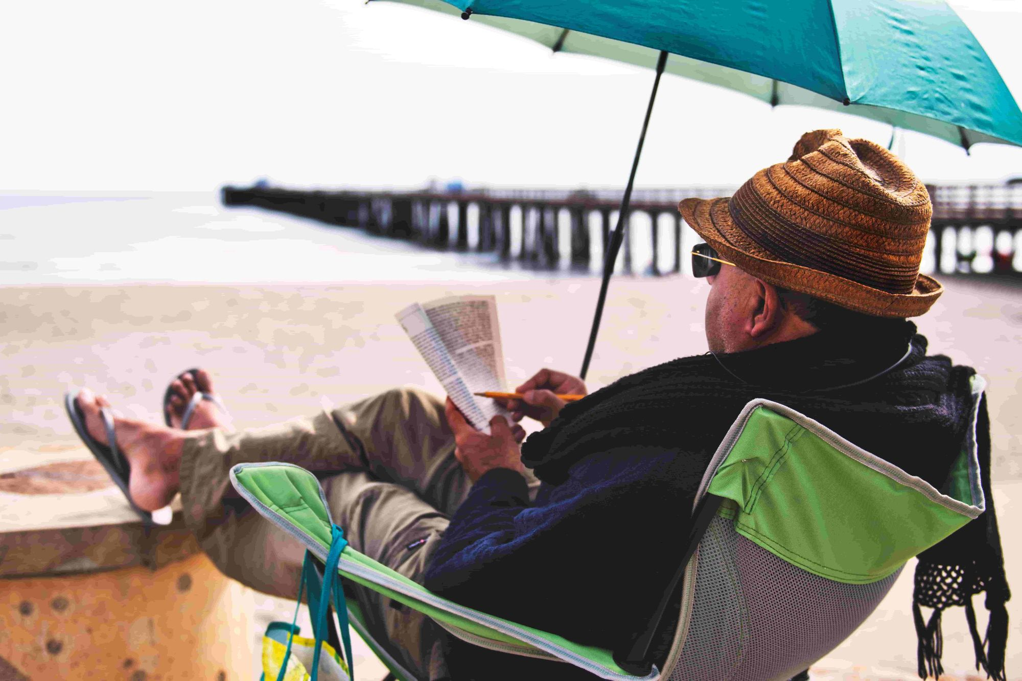 An older man sits on the beach, reading and making notes