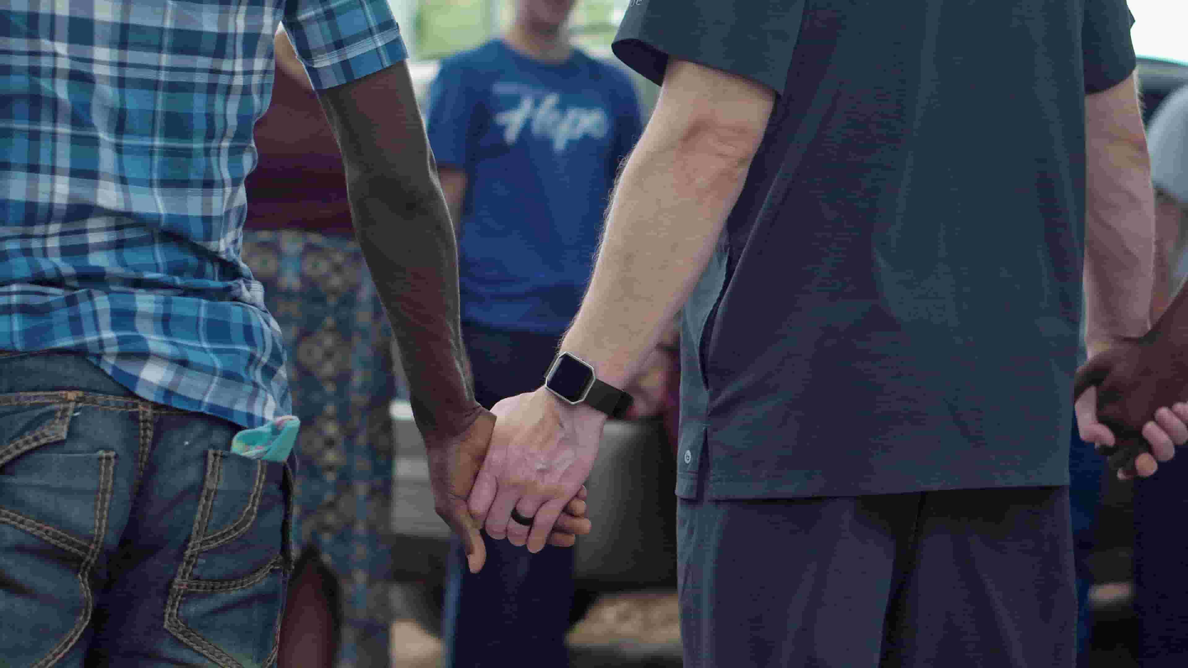 Two men hold hands, offering each other support