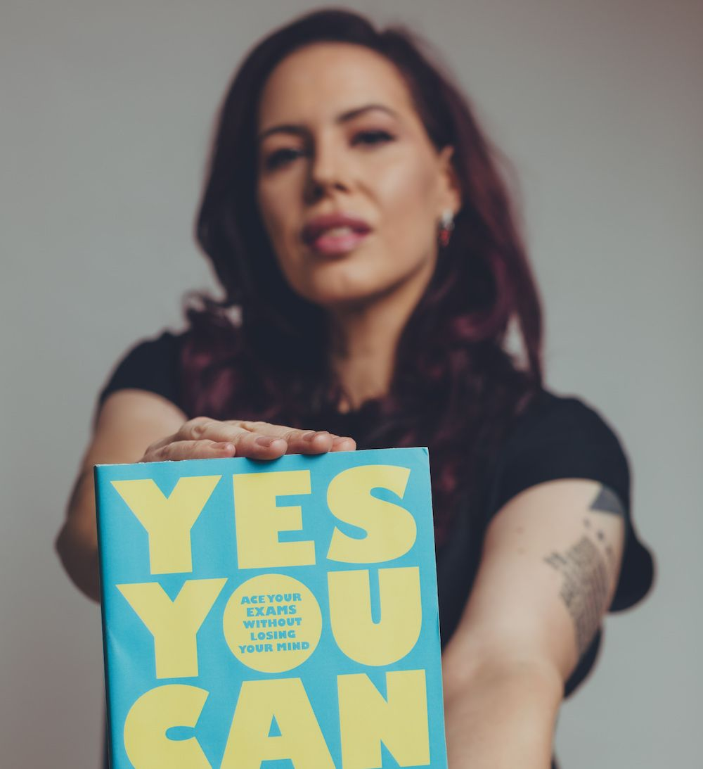 Natasha Devon holding her new book, Yes You Can
