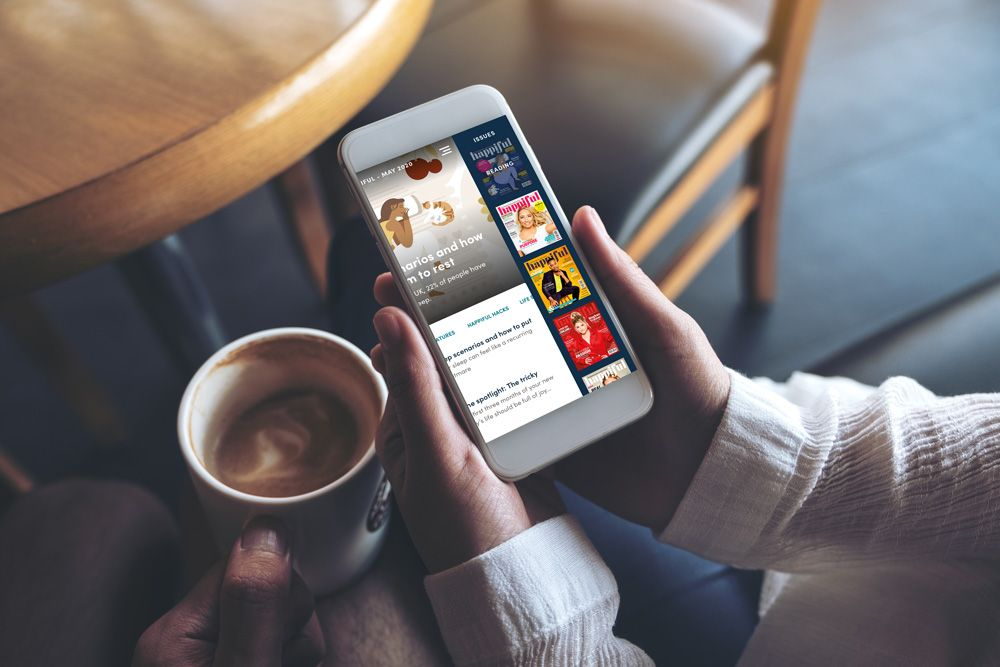 A persons hands using the Happiful App to read the magazine