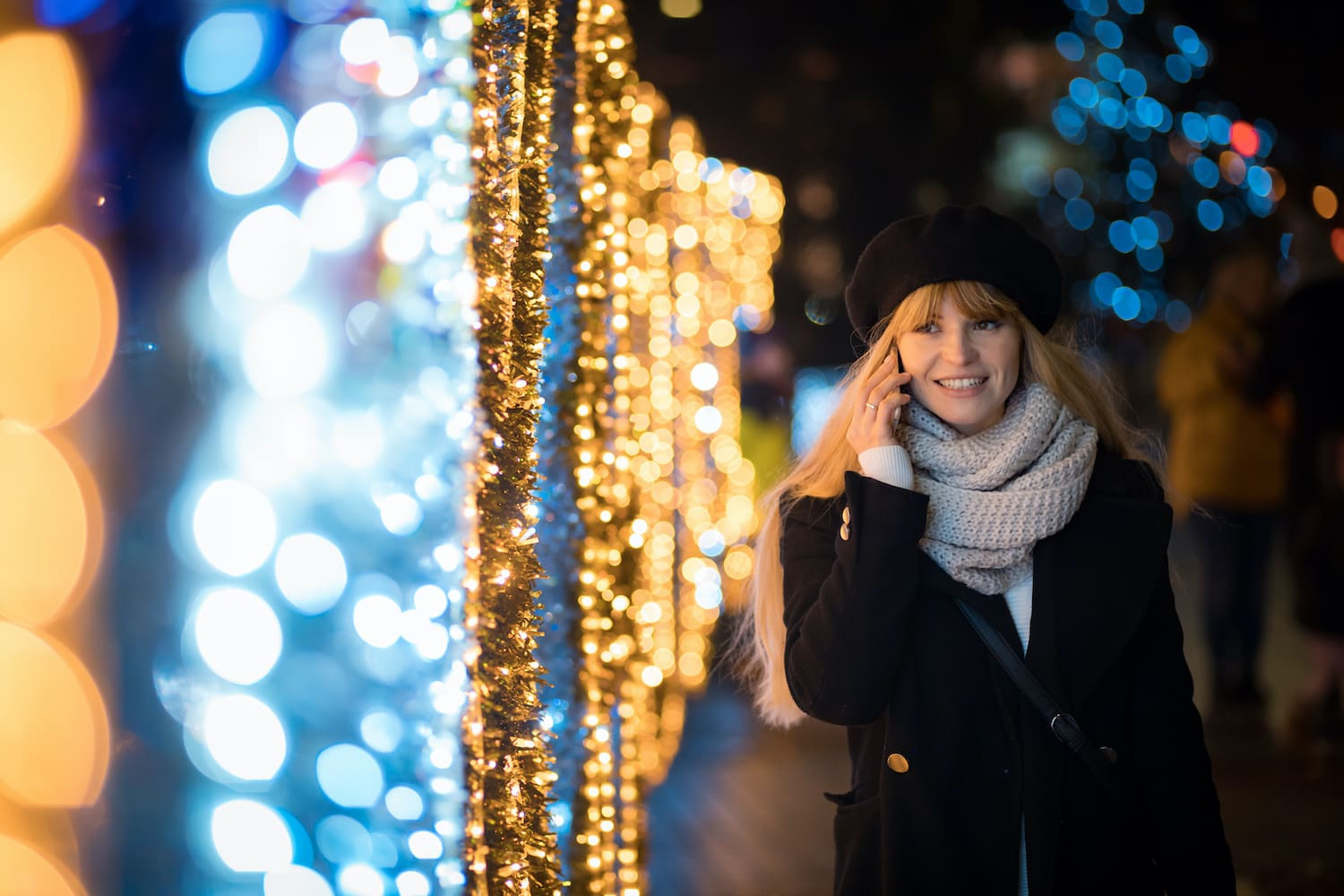 Woman talking on the phone whilst walking next to fairy lights
